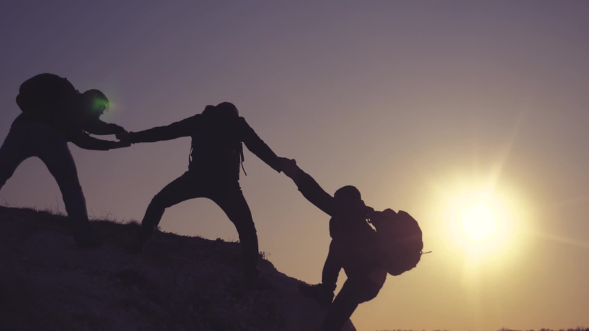 Teamwork help business travel silhouette concept. group team of tourists lends helping hand climb the cliffs mountains. teamwork people climbers climb to the top helping hand hardships the path