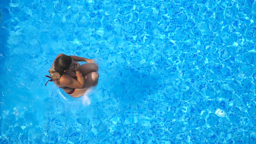 Top view of young woman jumping in pool and splashing crystal clear water. Unrecognizable girl resting and having fun on resort. Lady relaxing during summer vacation or holiday. Slow motion Close up   Shutterstock HD Video #1030854689