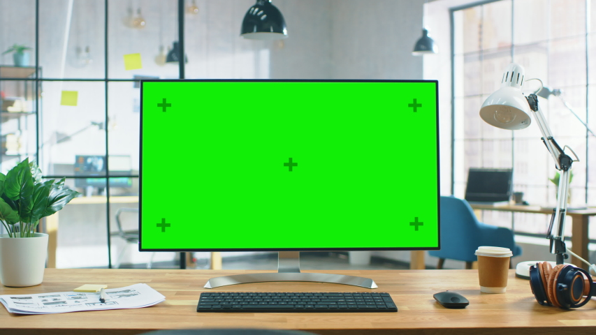 Wide Green Mock-up Screen Desktop Computer Standing on the Desk in the Modern Creative Office. In the Background High Ceiling Bright Creative Loft for Professional Developers and Designers | Shutterstock HD Video #1030863473