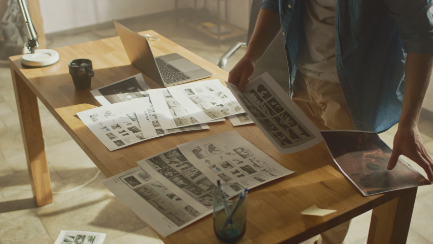 Creative Designer Works on a Storyboard, Looks at His Sketches and Concepts, Choosing the Best Drawings for His Project. Video Editing, Comics Compilation, Application UI or Game Plot. High Angle | Shutterstock HD Video #1030863542