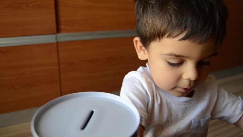 Cute two years old saving money, putting coins in metal bank. | Shutterstock HD Video #1030872314