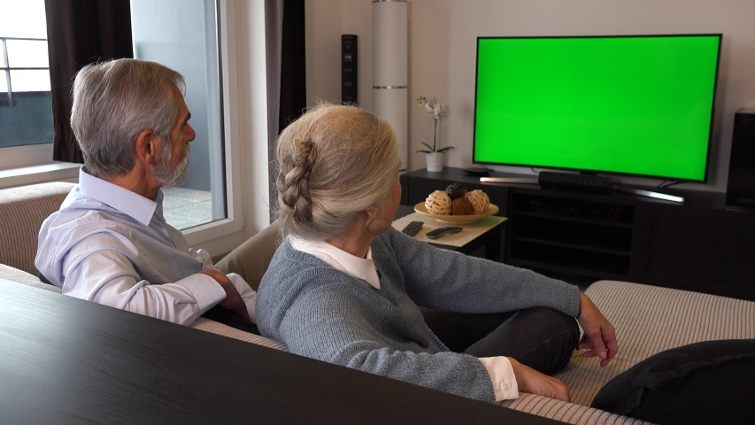 An elderly couple sits in a living room in an apartment, watches TV with a green screen, then turns and nods at the camera with a smile