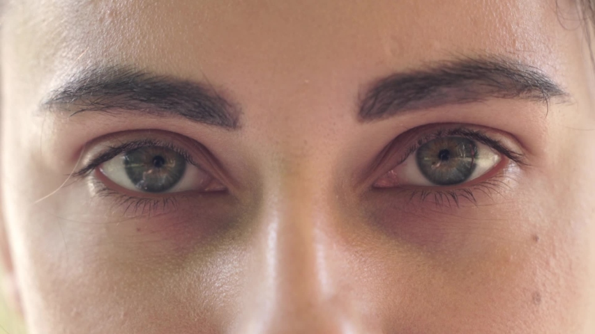Close-up of beautiful green female eyes. The girl opens her eyes