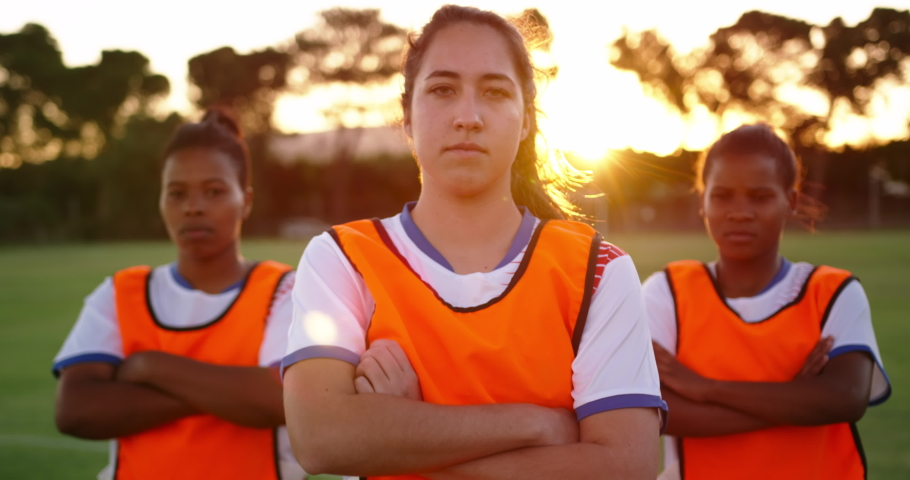 Front view close up of concentrated diverse female soccer team in orange vests standing with arms crossed on soccer field.