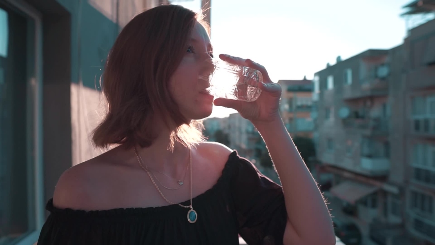 Beauty woman drinking water in glass and being happy at sunset time. Healthy life, nutrition concept slow motion footage.   | Shutterstock HD Video #1030907699
