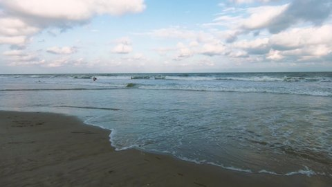 Waves gently crashing onto a sandy beach as sun sets over the horizon. Slow motion