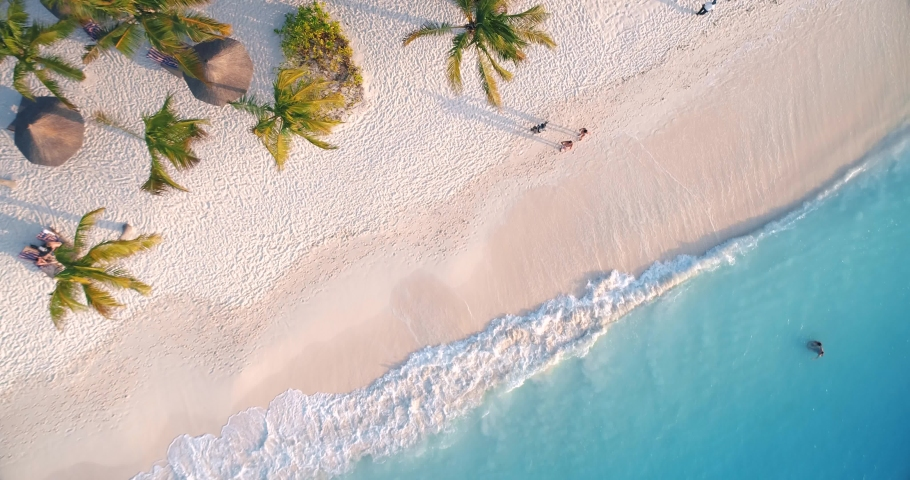 Aerial view of sea waves, umbrellas, palm trees and walking people on sandy beach at sunset. Summer in Zanzibar, Africa. Tropical landscape with parasols, sand, blue water. Top view from air. Travel #1030914140