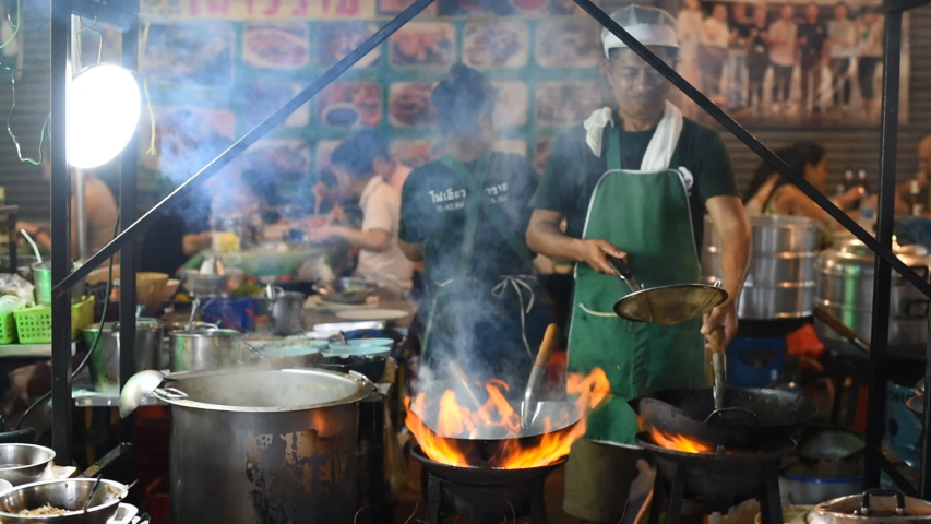 Bangkok, Thailand - June 5, 2019: a chef fries in a wok on the vast flame of the stove with rising vapor and smoke at a street cafe in an alley adjacent to Yaowarat Street, Chinatown.