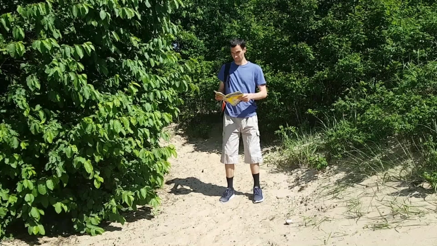 Man tourist out of the woods on the beach and unfolds the map. Terrain orientation. Hiking | Shutterstock HD Video #1030926203