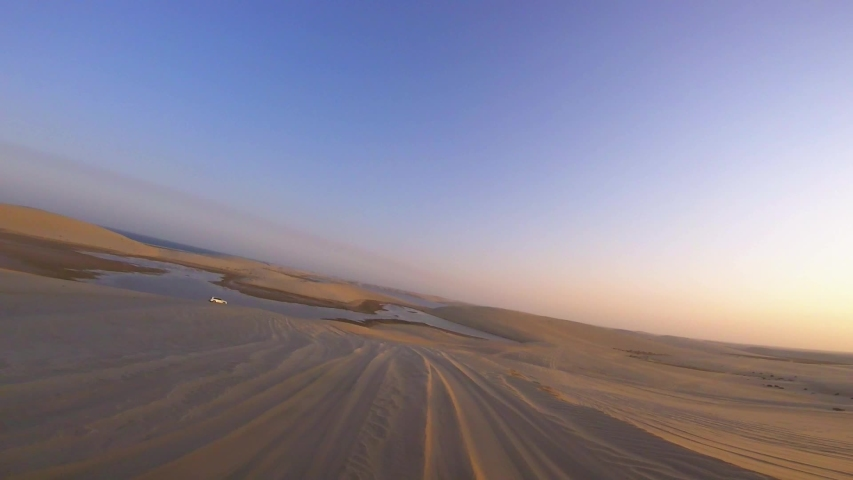 First person view, POV video as smoothly driving through huge sand dunes in a desert