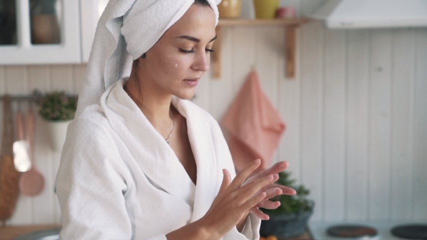 Close up of young woman in white bathrobe and with towel on head applies moisturizer cream on her face. Girl does daily beauty care cosmetic routine