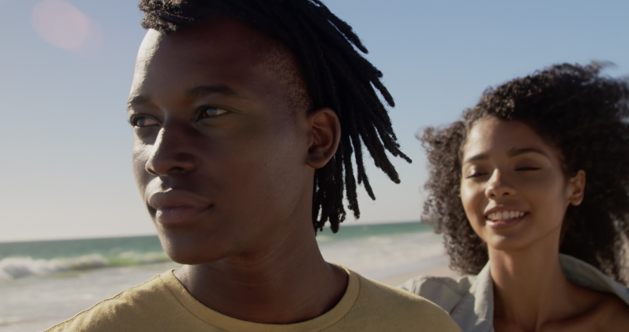 Front view close up of African american couple embracing each other on the beach. They are smiling