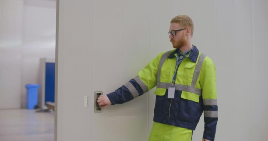 Young caucasian engineer opening door to the factory workshop #1030942820
