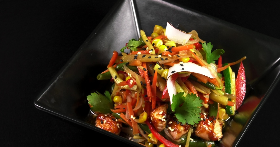 Asian noodles with vegetables and meat on a black background. | Shutterstock HD Video #1030943078
