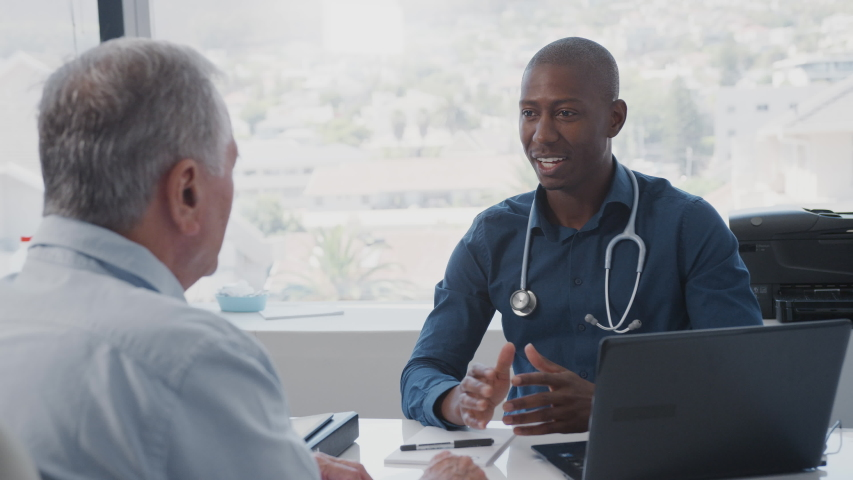 Senior Male Patient In Consultation Shaking Hands With Doctor Sitting At Desk In Office
