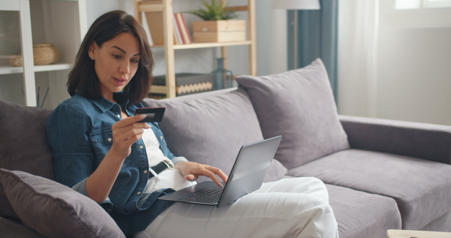 Pretty girl is making online payment holding bank card using modern laptop at home sitting on sofa and smiling. Finance, shopping in internet and youth concept.