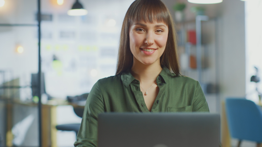 Young Beautiful Brunette Works on a Laptop Computer in Cool Creative Agency in a Loft Office. She has a Take-away Coffee and a Notebook on Her Table. Camera Zooms In and She Smiles and Laughs. | Shutterstock HD Video #1030955399