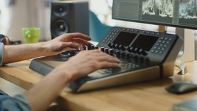 Close Up Shot of Video Editor's Hands Working with Footage on His Personal Computer Using an Editing Console Deck. He Works in Cool Office Loft. Laptop and Headphones Lie on the Table.