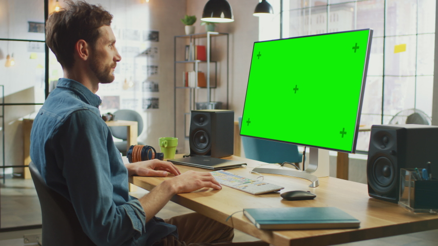 Young Professional Creative Employee Works on His Personal Computer with Big Green Screen Mock Up Display. He Works in a Cool Office Loft. Creative Man Puts Headphones On. | Shutterstock HD Video #1030955576