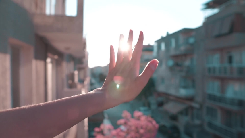 Waving hand to glare of sun flare in afternoon time, urban street. Woman's hand on balcony, sunbeams an gesture.