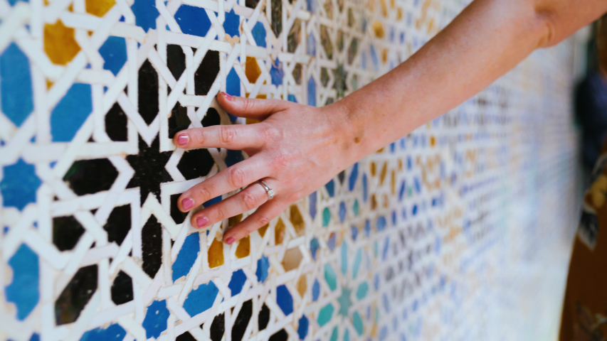 SEVILLE, SPAIN - MAY 9, 2019: Closeup of a hand brushing along ornate colorful mosaic tile pattern in Royal Alcazar