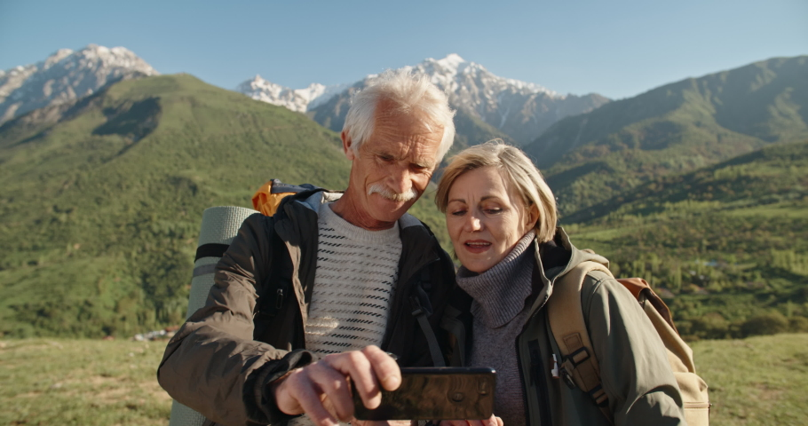 Old couple having a hike in spring mountains, then stopping to take a picture on a smartphone. Senior caucasian family spending time together travelling after retirement - tourism concept 4k | Shutterstock HD Video #1030971950