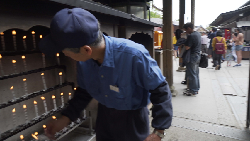 kyoto, kansai / Japan - 04 29 2018: Employee lighting candles in Japan