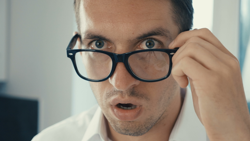 Portrait of young man is surprised and takes off his glasses in shock. He is worried about seeing | Shutterstock HD Video #1030983140