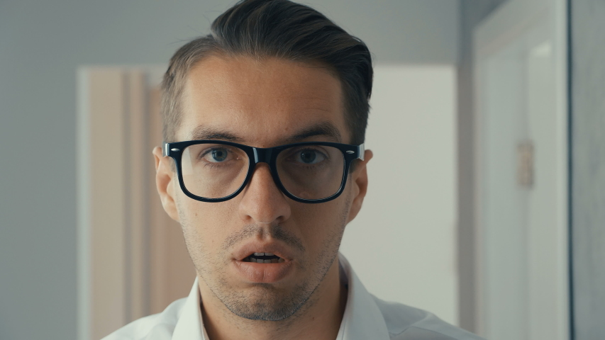 Portrait of young man is surprised and takes off his glasses in shock. He is worried about seeing   Shutterstock HD Video #1030983149