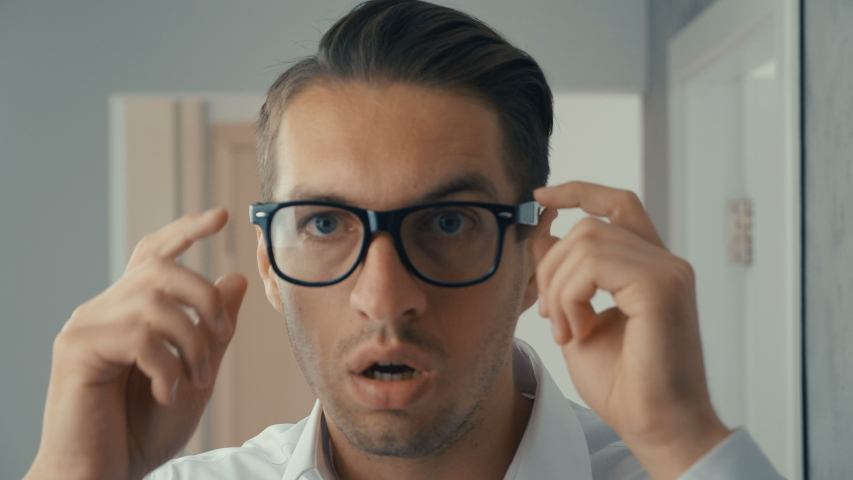 Portrait of young man is surprised and takes off his glasses in shock. He is worried about seeing | Shutterstock HD Video #1030983158