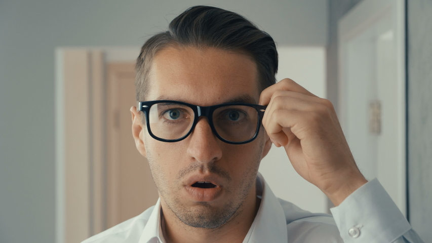 Portrait of young man is surprised and takes off his glasses in shock. He is worried about seeing   Shutterstock HD Video #1030983161