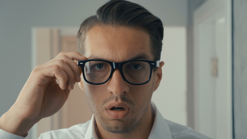 Young man is shocked and surprised. A man in surprise shoots glasses and looks at the camera in surprise.