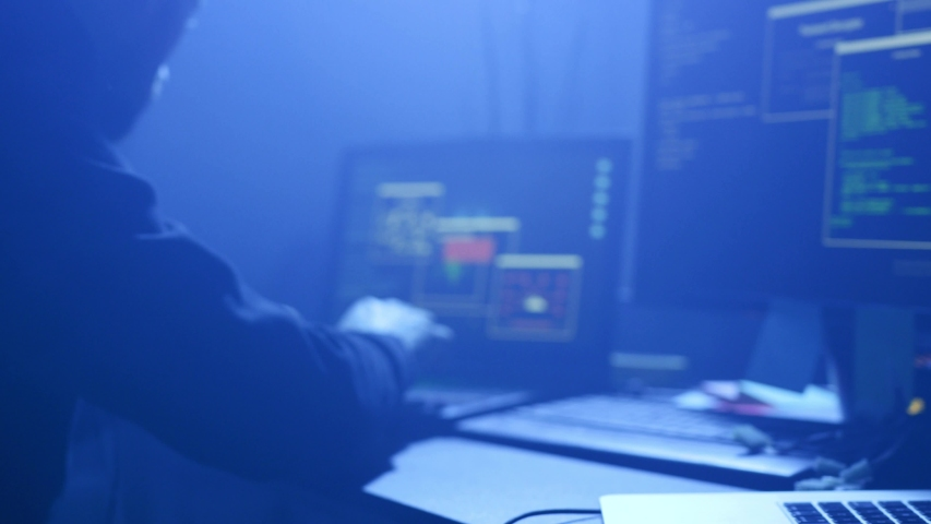 Busy computer hacker working with codes break into corporate data servers in the office at night. Royalty-Free Stock Footage #1030984118