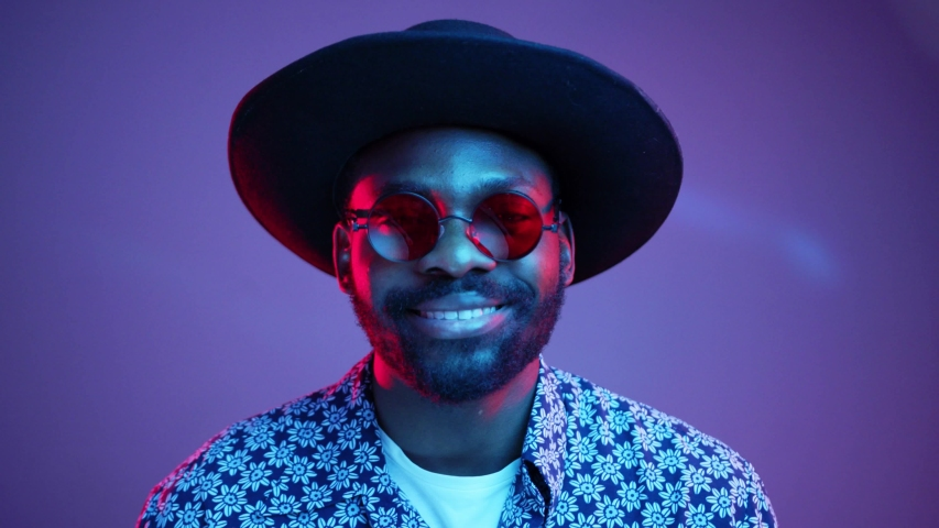 Cheerful stylish Afro American hipster man in trendy hat and stylish steampunk polarized eyeglasses attractively smiling straight to camera on bright colorful neon lights. Studio portrait. Style, new | Shutterstock HD Video #1030984271