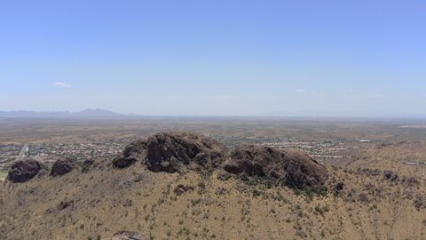 Gorgeous drone clip of desert mountain with homes in background and clear blue skies in Arizona. Aerial footage.