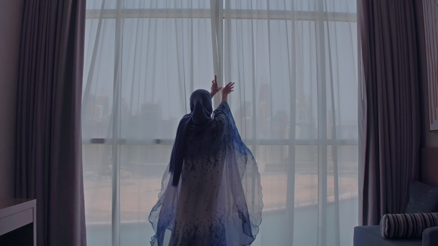 Young Muslim woman in Islam traditional blue dress at home uncovering window with city view. Dubai city on the background. | Shutterstock HD Video #1031000510