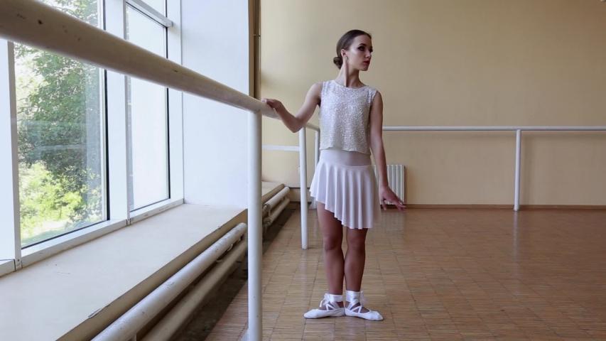 Young thin ballerina in white dress dancing near a big window. #1031006141
