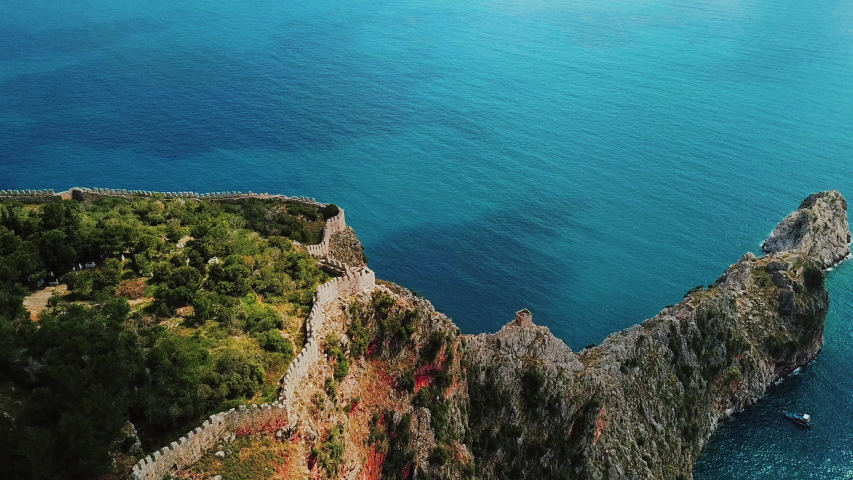 Aerial view around ruins and ancient historic Alanya fortress walls on rocky hills and riffs at background of azure mediterranean sea with sailing ship. Antalya Province, Turkey, 4k footage.