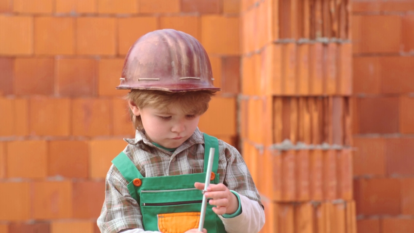 Childhood concept. Little boy dreaming about a new home. Son helper. Child and works. Cute boy building house | Shutterstock HD Video #1031036189