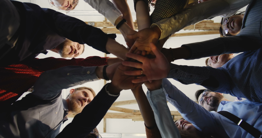 Close-up happy diverse adult business people joining hands together. Team spirit at modern multiethnic loft office. | Shutterstock HD Video #1031049032