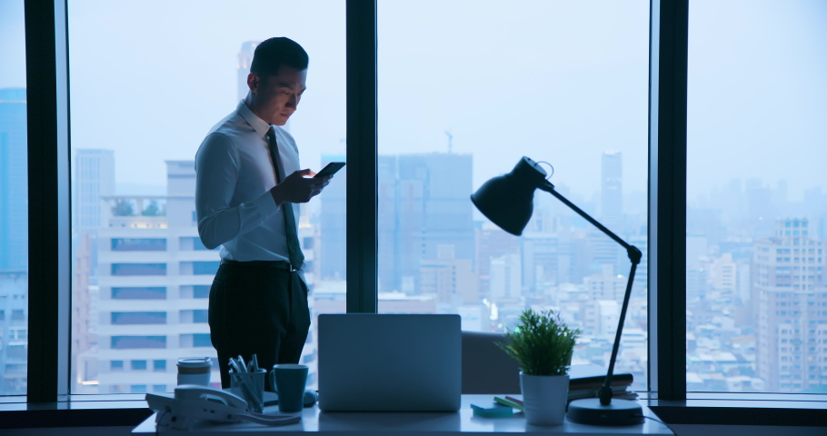 Asian businessman use cellphone at night in the office | Shutterstock HD Video #1031049875
