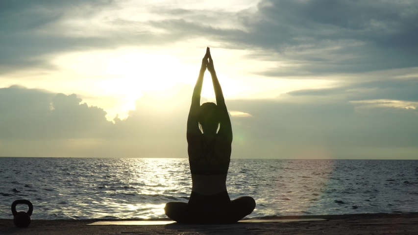Silhouette young woman practicing yoga on the beach at sunset. 4K Resolution   Shutterstock HD Video #1031060984