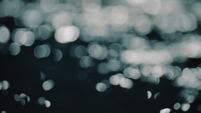 Bokeh sun glare reflected in water surface. Sunrays flickering in water stream. The shimmering small sea waves in sun. Abstract blurry out of focus bokeh background imagery. Slow motion, 4k footage