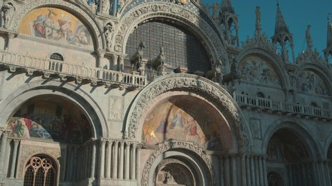 Italy, Venice, February 2019. Beautiful ancient facade with raised cupolas in gothic style. The whole basilica facade covered in beautiful mosaic.