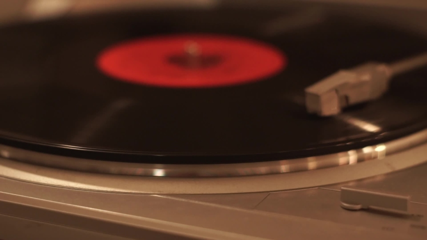 Modern turntable with spinning vintage vinyl record, close-up. Dropping stylus needle on old vinyl disc with red sticker. Silver colored stereo record player playing music under warm muffled light.