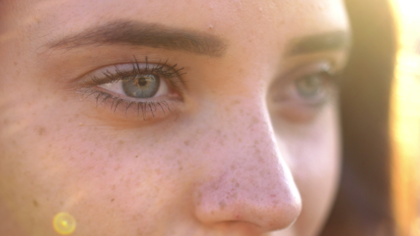 Close up of woman's face at sunset, beautiful green eyes, portrait, outdoor relax sunlight, slow motion. Royalty-Free Stock Footage #1031075549