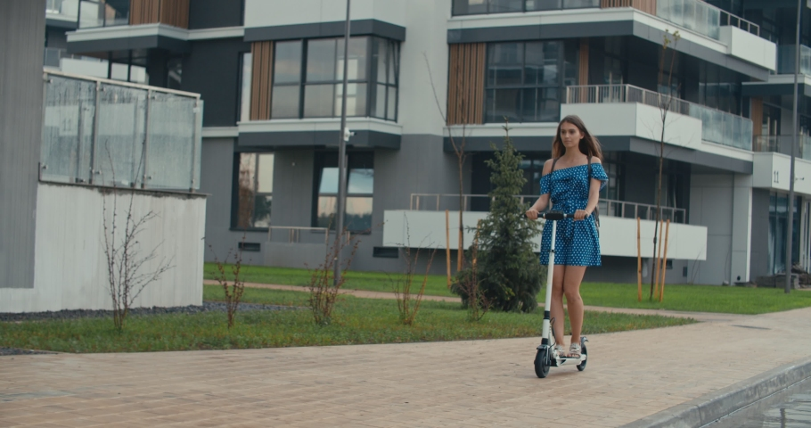 Rainy day. Attractive girl riding the electric kick scooter to work or study. 4K slow motion raw video footage 60 fps | Shutterstock HD Video #1031084285