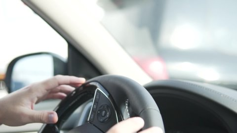 men's hand turns the leather steering wheel. A man drives a car, close-up steering