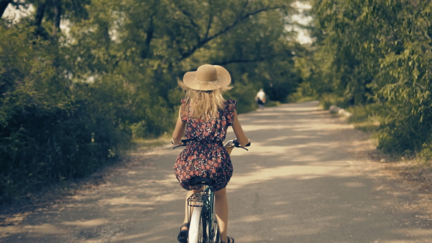 Cyclist Happy Travel Woman On Bicycle.Hair Blowing Girl Cycling.Handsome Female In Hat Cycling On Bike.Beautiful Woman Hair Fluttering.Adorable Cyclist Girl In Dress Workout.Vacation Holiday Fun Sport
