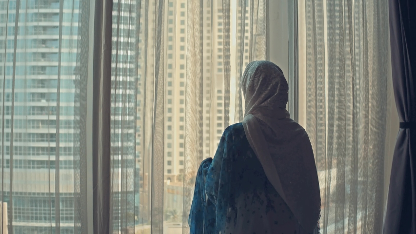 Silhouette of young Arab woman weared in traditional dress abaya opens curtains on the big window stretches arms and looking out her apartment on the city buildings during amazing sunrise. Dubai city